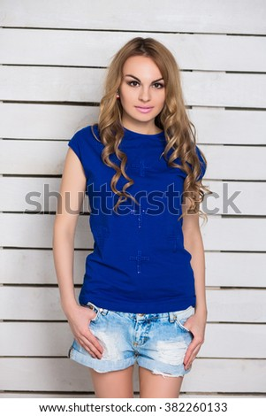 Portrait of young blonde in jeans shorts and blue t-shirt posing near the white wooden wall - stock photo