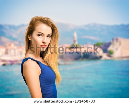 Portrait of Young Blonde Woman in Blue Top Standing at Sea. Beautiful Summer Resort Concept. Shallow Depth of Field. Copy Space. - stock photo