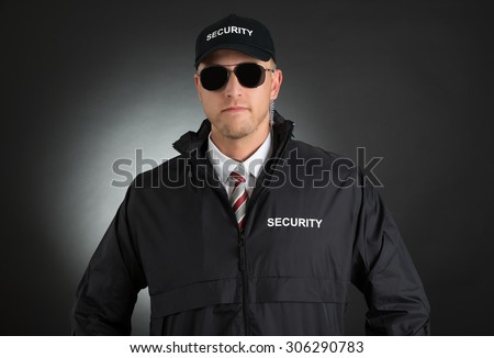 Portrait Of Young Bodyguard In Uniform Wearing Sunglasses Over Black Background - stock photo