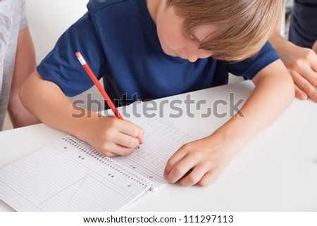 Portrait of young boy doing homework at home - stock photo