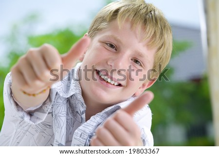Portrait of young boy giving his thumbs up - stock photo