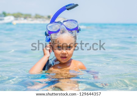 Portrait of young boy in snorkling equipment swimming in the transparent sea - stock photo