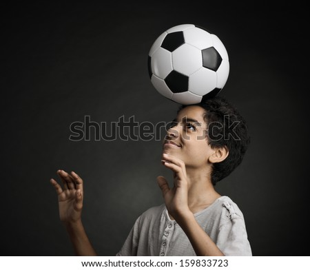 Portrait of young boy playing with a soccerball - stock photo