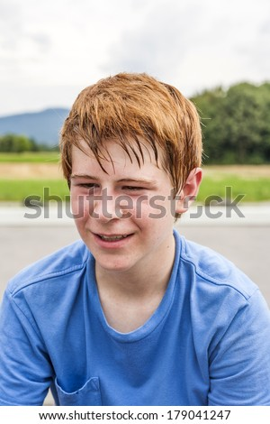 portrait of young boy resting at the skate park - stock photo