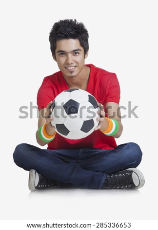 Portrait of young boy smiling while holding soccer ball over white background - stock photo
