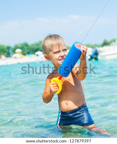 Portrait of young boy swimming and plaing water pistol in the transparent sea - stock photo