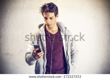 Portrait of young boy using mobile phone with headphones  - stock photo