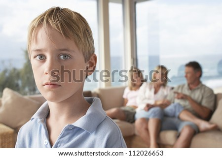Portrait of young boy with family in background at home - stock photo
