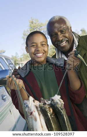 Portrait of young boy with grandfather holding freshly caught fishes - stock photo