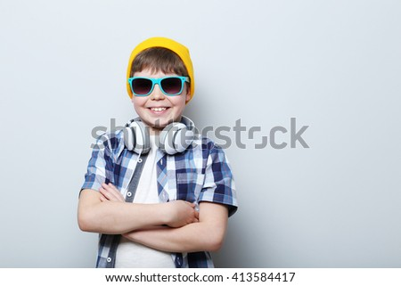 Portrait of young boy with headphones on grey background - stock photo