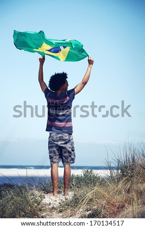 Portrait of young Brazilian man with Brasil flag supporting soccer team for world cup - stock photo