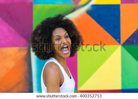 Portrait of Young Brazilian woman smiling on colorful background - stock photo