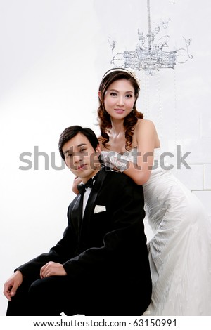 Portrait of young bride and groom in romantic action on white background - stock photo