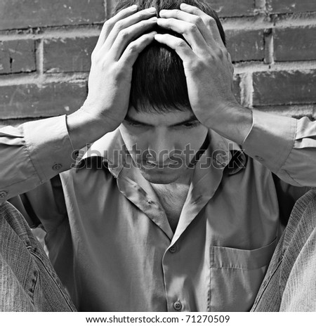 portrait of young brunet guy in depression sitting near red brick wall - stock photo