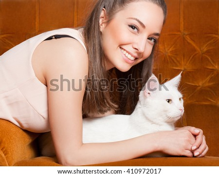 Portrait of young brunette beauty holding gorgeous white cat. - stock photo