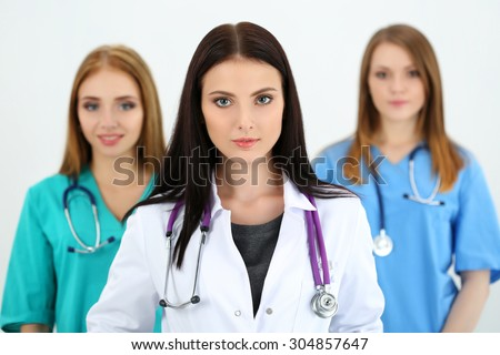 Portrait of young brunette female doctor surrounded by medical team, looking at camera. Healthcare and medicine concept. - stock photo