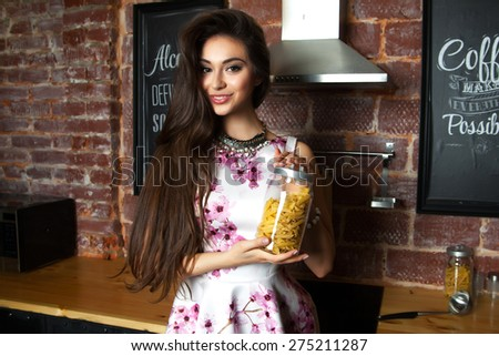 Portrait of young brunette girl cooking.Holding a packet of pasta in her hands.Stylishly dressed in white summer flower dress.Cheerful girl smile and showing emotions,ready to cook,pasta,cooking - stock photo
