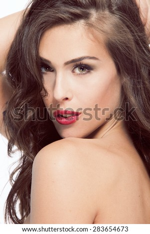 portrait of young brunette woman looking straight to camera - stock photo