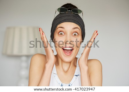 Portrait of young brunette woman wearing headband and sunglasses on her head screaming with excitement and joy.  Headshot of happy excited female with winning expression on her face, mouth wide open - stock photo