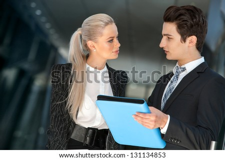 Portrait of young business colleagues with file discussing work. - stock photo