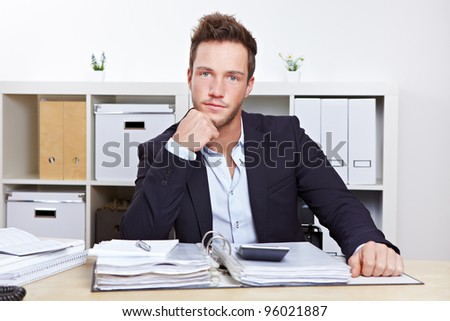 Portrait of young business man at desk in office - stock photo