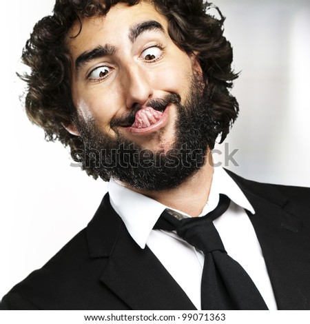 portrait of young business man showing the tongue indoor - stock photo