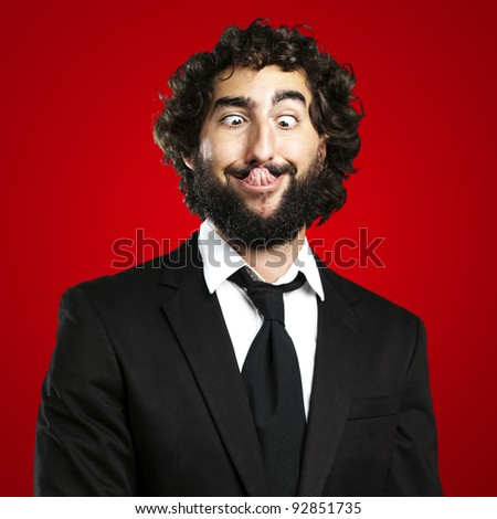 portrait of young business man showing the tongue over red background - stock photo