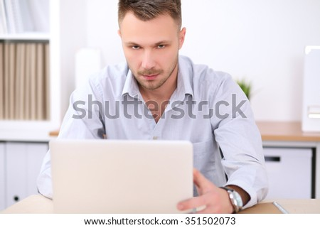 Portrait of young business man sitting at the desk on office background.  - stock photo