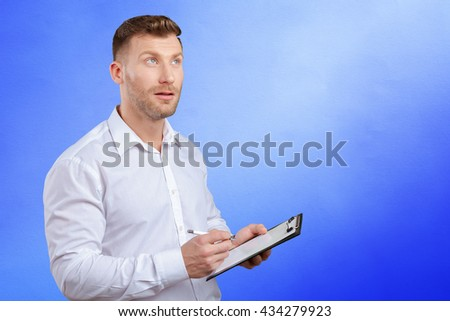 Portrait of young business man taking notes - stock photo