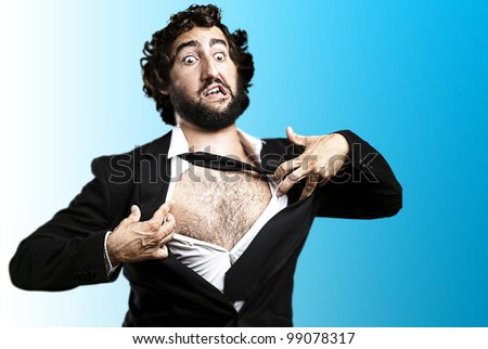 portrait of young business man tearing his suit over blue - stock photo