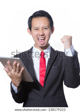 Portrait of young business man using tablet feeling success - stock photo