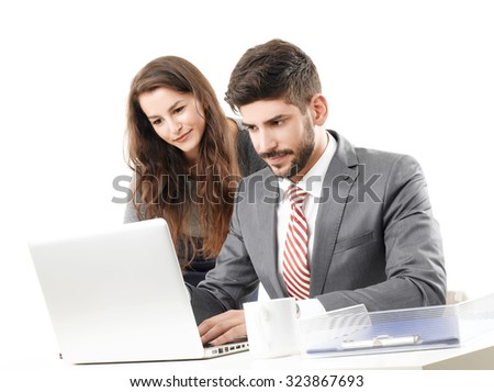 Portrait of young business people working together. Professional man sitting in front of laptop and typing on keyboard while businesswoman standing next to him. Isolated on white background.  - stock photo