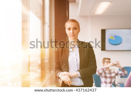 portrait of young business woman at modern startup office interior team in meeting group in background - stock photo