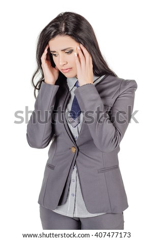 portrait of young business woman in grey suit with a huge headache holding head. isolated on white background. business and lifestyle concept. - stock photo