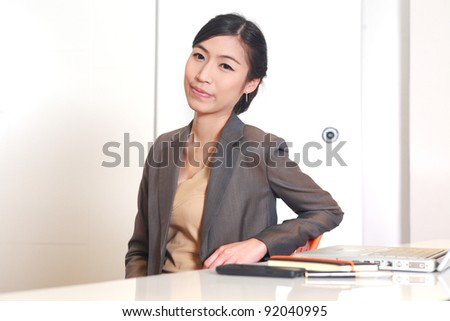 Portrait of young business woman sitting at her desk with a smile - stock photo