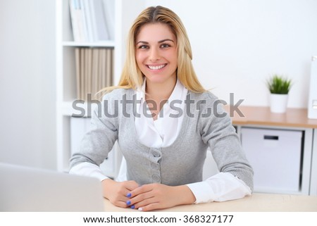 Portrait of young business woman sitting at the desk on office background - stock photo