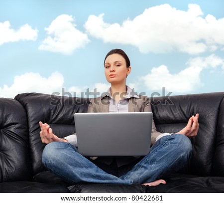Portrait of young business woman sitting with a laptop on comfortable black couch and meditating on cyan sky background - stock photo
