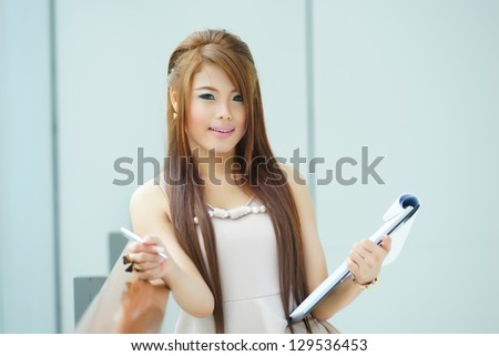 Portrait of young business woman standing near window in modern office and writing notes - stock photo