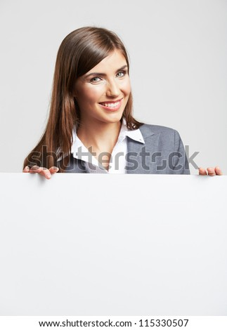 Portrait of young business woman with blank white board on gray isolated - stock photo