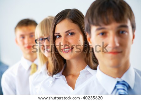 Portrait of young business woman with her colleagues standing in a row - stock photo
