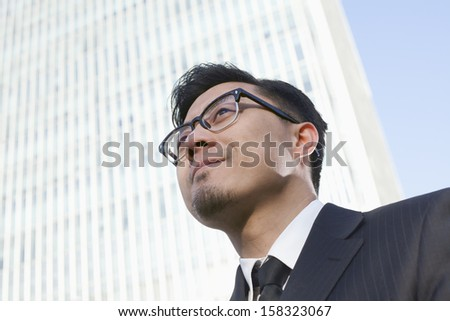 Portrait of young businessman by the world trade center in Beijing - stock photo