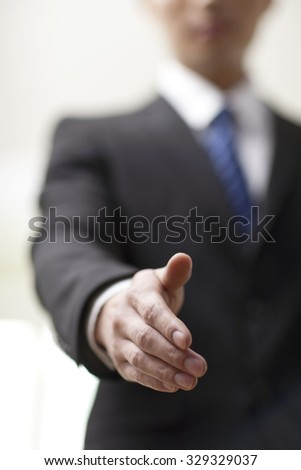 Portrait of young businessman executives extending hands to shake,close-up - stock photo