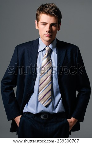 Portrait of young businessman-gray background - stock photo