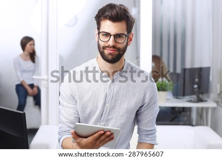 Portrait of young businessman holding digital tablet in his hands while looking at camera and smiling. Business team working at background. - stock photo