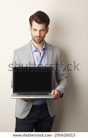 Portrait of young businessman holding laptop in his hand. Showing the screen. Small business. - stock photo