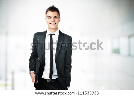 Portrait of young businessman holding laptop smiling. - stock photo