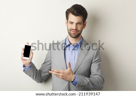 Portrait of young businessman holding mobile in his hands while standing in front of wall. Business people. - stock photo