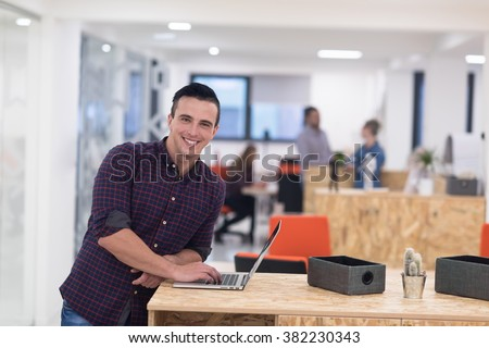 portrait of young businessman in casual clothes at modern  startup business office space,  working on laptop  computer - stock photo