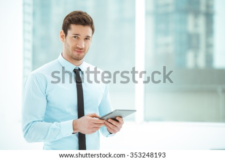 Portrait of young businessman in office with big window. Businessman using tablet computer and looking at camera - stock photo
