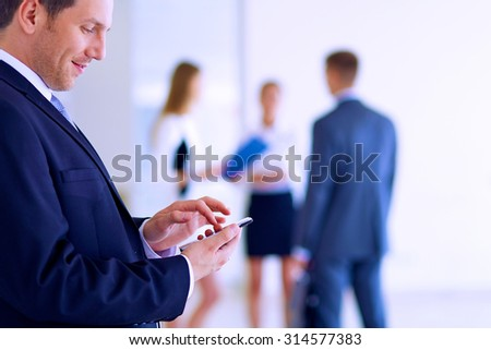 Portrait of young businessman in office with colleagues in the background - stock photo